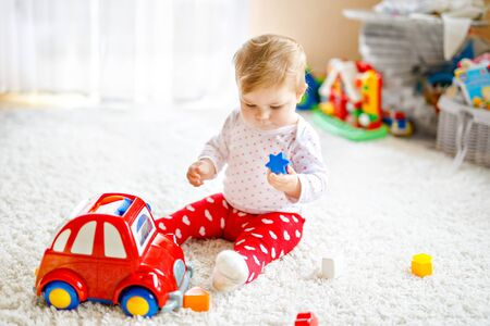Adorable cute beautiful little baby girl playing with educational wooden toys at home or nursery. Healthy happy toddler with colorful red car indoors. child learning colors and forms Foto de archivo - 129325449