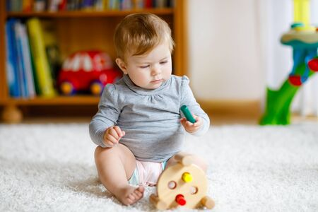 Adorable baby girl playing with educational toys . Happy healthy child having fun with colorful different wooden toy at home. Early development for children with nature toy. Foto de archivo - 129325462