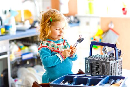 Cute little toddler girl helping in the kitchen with dish washing machine. Happy healthy blonde child sorting knives, forks, spoons, cutlery. Baby having fun with helping housework mother and father. Foto de archivo - 129325463