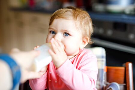 Cute adorable baby girl holding nursing bottle and drinking formula milk. First food for babies. New born child, sitting in chair of domestic kitchen. Healthy babies and bottle-feeding concept Foto de archivo - 129325475