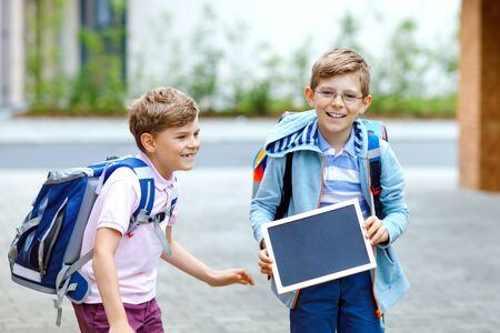 Two little kid boys with backpack or satchel. Schoolkids on the way to school. Healthy children, brothers and best friends outdoors on street leaving home. Schools out on chalk desk. Happy siblings.