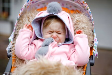 Sad crying little beautiful baby girl sitting in the pram or stroller on autumn day. Unhappy tired and exhausted child in warm clothes, fashion stylish pink baby coat with bunny ears. 스톡 콘텐츠