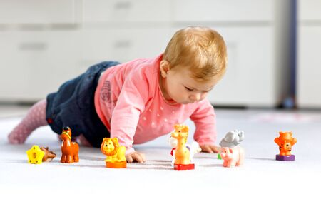 Adorable baby girl playing with domestic toy pets like cow, horse, sheep, dog and wild animals like giraffe, elephant and monkey. Happy healthy child having fun with colorful different toys at home Foto de archivo - 129325474