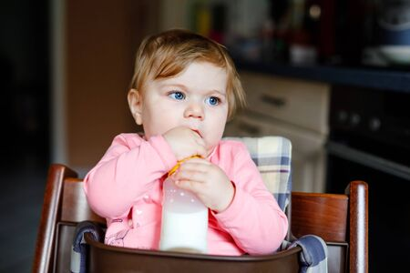 Cute adorable baby girl holding nursing bottle and drinking formula milk. First food for babies. New born child, sitting in chair of domestic kitchen. Healthy babies and bottle-feeding concept Foto de archivo - 129325548