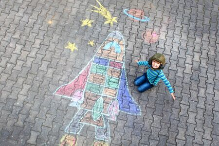 little kid boy flying by a space shuttle chalks picture Imagens