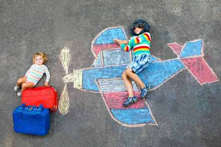 Two little children, kid boy and toddler girl having fun with with airplane picture drawing with colorful chalks on asphalt. Siblings painting with chalk and going on vacations. Foto de archivo - 129325555