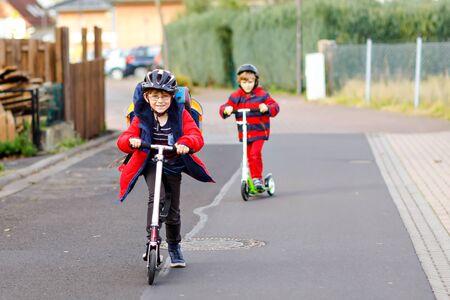Zwei kleine Kinderjungen, die auf dem Weg zur oder von der Schule auf Schieberollern fahren. Schüler von 7 Jahren fahren durch Regenpfütze. Lustige Geschwister und beste Freunde, die zusammen spielen. Kinder nach der Schule