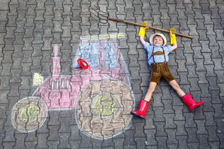 little kid boy having fun with tractor chalks picture Imagens