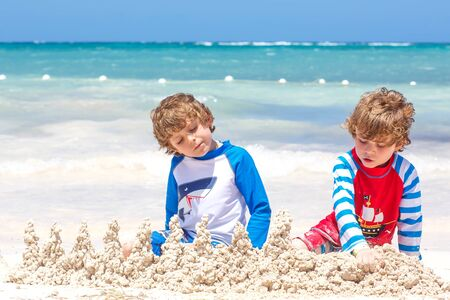Two little kids boys having fun with building a sand castle on tropical beach on island. Healthy children playing together on their vacations. Twins, Happy brothers laughing and smiling
