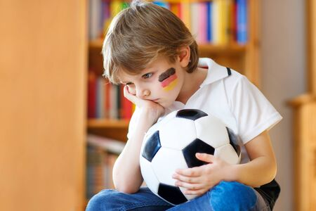 Sad and not happy little kid with football about lost football or soccer game. child after watching match on tv Stockfoto