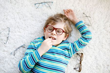 Close-up portrait of little blond kid boy with brown eyeglasses Фото со стока - 130050553