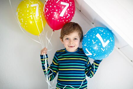 Portrait of happy kid boy with bunch on colorful air balloons on 7 birthday