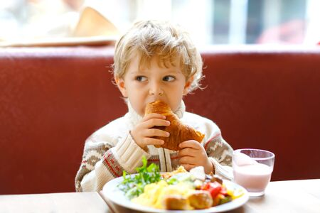 Cute healthy kid boy eating croissant and drinking strawberry milkshake in cafe. Happy child having breakfast with parents or at nursery. Vegetables, eggs as healthy food for children. Фото со стока