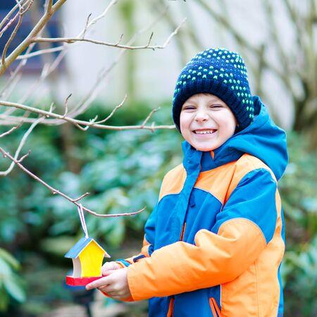 Petit garçon enfant nourrissant les oiseaux en hiver. Enfant d'âge préscolaire heureux mignon suspendu maison d'oiseau colorée sur un arbre par une journée froide et glaciale. Enfant d'âge préscolaire dans des vêtements wam colorés. Nature, empathie avec les animaux. Banque d'images