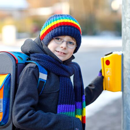 Little school kid boy of elementary class walking to school during snowfall. Happy healthy child with glasses pushing button for traffic lights. With backpack or satchel in colorful winter clothes. Banque d'images