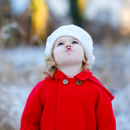 Outdoor winter portrait of little cute toddler girl in red coat and white fashion hat barret. Healthy happy baby child walking in the park on cold day with snow and snowfall. Stylish clothes for kids.
