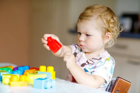 Adorable toddler girl playing with educational toys in nursery. Happy healthy child having fun with colorful different plastic blocks at home. Cute baby learning creating and building. 写真素材 - 130050701