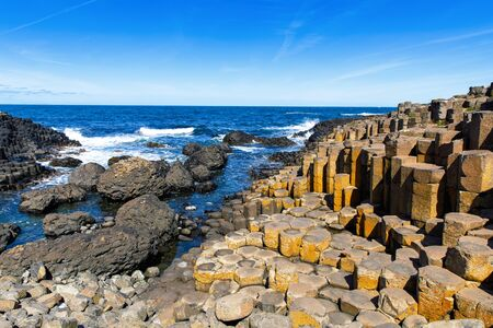 Landscape of Giants Causeway trail with a blue sky in summer in Northern Ireland, County Antrim. UNESCO heritage. It is an area of basalt columns, the result of an ancient volcanic fissure eruption