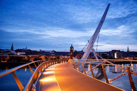 Derry, Irland. Beleuchtete Friedensbrücke in Derry Londonderry, Kulturstadt, in Nordirland mit Stadtzentrum im Hintergrund. Nacht bewölkter Himmel mit Reflexion im Fluss in der Abenddämmerung