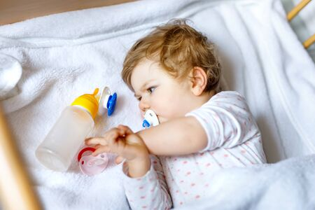 Cute little baby girl holding bottle with formula mild and drinking. Child in baby cot bed before sleeping