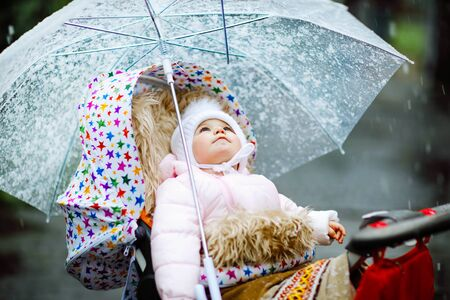 Cute little beautiful baby girl sitting in the pram or stroller on cold day with sleet, rain and snow. Happy smiling child in warm clothes, fashion stylish baby coat. Baby with big umbrella 版權商用圖片