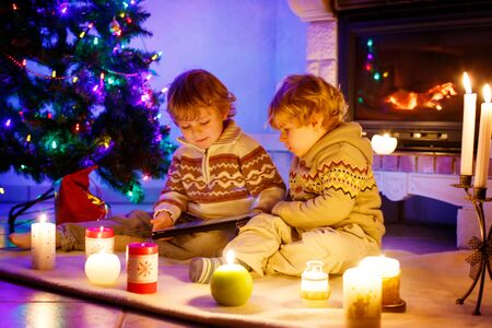 Two cute toddler boys, blond twins playing with new tablet gift. Family celebrating Christmas holiday