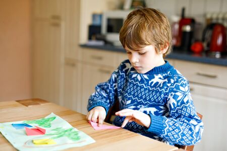 Little kid boy making paper origami tulip flowers for a postcard for mothers day or birthday. Cute child of elementary class school doing handicraft Banco de Imagens