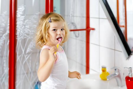 Cute adorable toddler girl holding toothbrush and brushing first teeth in bathroom after sleeping. Gorgeous baby child learning to clean milk tooth. Morning healthy hygiene routine for children