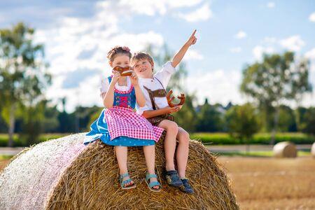 Zwei Kinder in traditionellen bayerischen Kostümen im Weizenfeld. Deutsche Kinder essen während des Oktoberfestes Brot und Brezel. Jungen und Mädchen spielen bei Heuballen während der Sommererntezeit in Deutschland.