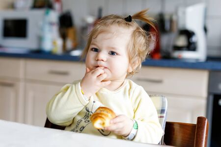 Happy little baby girl eating fresh croissant for breakfast or lunch. Healthy eating for children