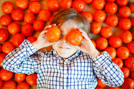 Adorable little kid boy with mandarin oranges background. Happy smiling child having fun with lot of fruits. Healthy food, eating and lifestyle concept 스톡 콘텐츠 - 130051109