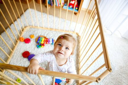 Beautiful little baby girl standing inside playpen. Cute adorable child playing with colorful toys. Home or nursery, safety for kids. Alone baby waiting for mom
