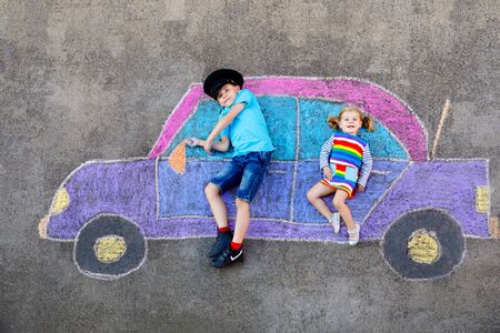 Two little children, kid boy and toddler girl having fun with with car picture drawing with colorful chalks on asphalt. Siblings painting on ground and playing together. Creative leisure for children