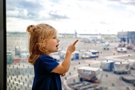 Cute little toddler girl at the airport, traveling. Happy healthy child waiting near window and looking at planes. Family going on vacations by airplane. Canceled flight due to pilot strike.