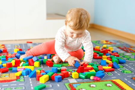 Adorable baby girl playing with educational toys . Happy healthy child having fun with colorful different wooden blocks at home in domestic room. Baby learning colors and forms