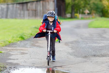 cute little school kid boy riding on push scooter on the way to or from school. Schoolboy of 7 years driving through rain puddle. funny happy child in colorful fashion clothes and with helmet. Banco de Imagens