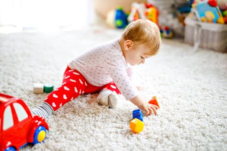 Adorable cute beautiful little baby girl playing with educational wooden toys at home or nursery. Healthy happy toddler with colorful red car indoors. child learning colors and forms Stock fotó