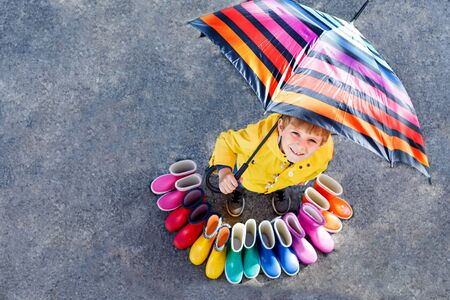 Little kid boy and group of colorful rain boots. Blond child standing under umbrella. Stock Photo