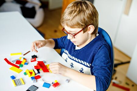 Little blond child with eye glasses playing with lots of colorful plastic blocks. Adorable school kid boy having fun with building and creating robot. Creative leisure modern technic and robotic.
