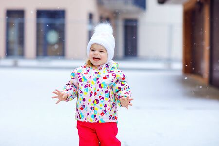 Portrait of little toddler girl walking outdoors in winter. Cute toddler eating sweet lollypop candy. Child having fun on cold snow day. Wearing warm baby colorful clothes and hat with bobbles.