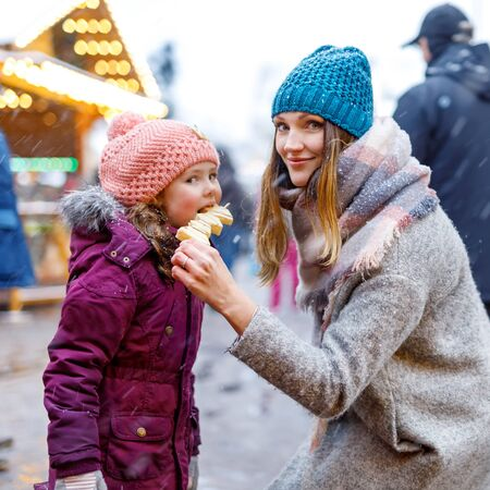 Young mother and daughter eating white chocolate covered fruits on skewer on traditional German Christmas market. Happy girl and woman on traditional family market in Germany, Munich during snowy day. Standard-Bild - 131455506
