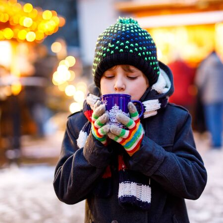 Little cute kid boy drinking hot children punch or chocolate on German Christmas market. Happy child on traditional family market in Germany, Laughing boy in colorful winter clothes. Zdjęcie Seryjne