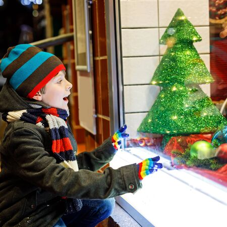 Cute little school kid boy on Christmas market. Funny happy child in fashion winter clothes making window shopping decorated with gifts, xmas tree. holidays, christmas, childhood and people concept Standard-Bild - 131457080