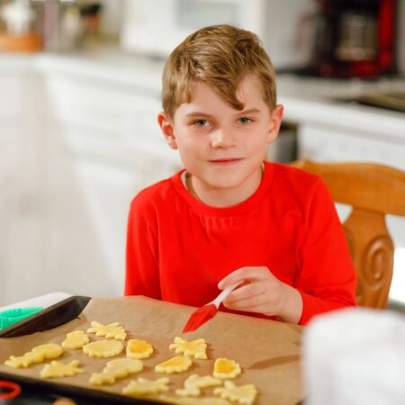 Cute little boy baking gingerbread Christmas cookies at home. Adorable blond child having fun in domestic kitchen. Traditional leisure with kids on Xmas.