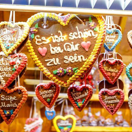 Gingerbread Hearts at German Christmas Market. Nuremberg, Munich, Fulda, Berlin, Hamburg xmas market in Germany. In German language It is beautiful to be with you.