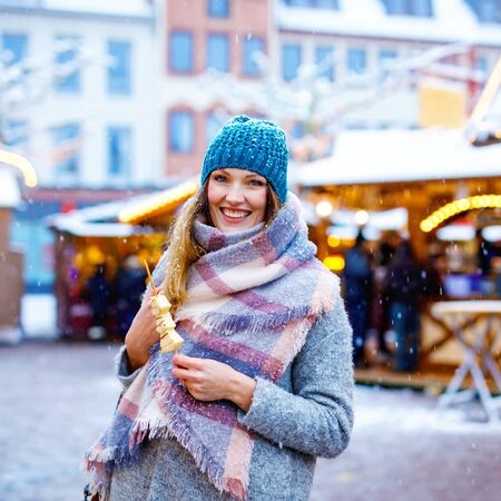 Beautiful young woman eating white chocolate covered fruits on skewer on traditional German Christmas market. Happy girl on traditional family market in Germany, Berlin during snowy day.