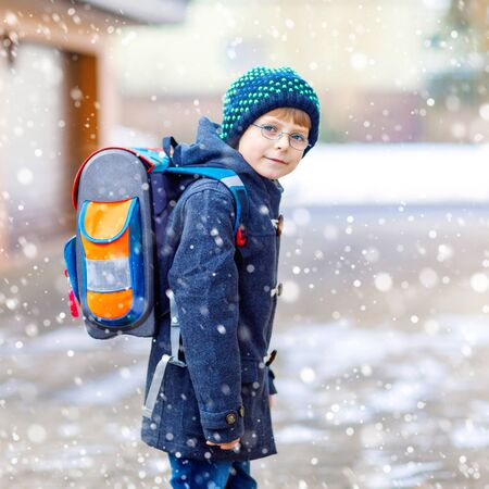 Little school kid boy of elementary class walking to school. Happy child having fun and playing with first snow. Student with backpack in colorful winter clothes. School building.