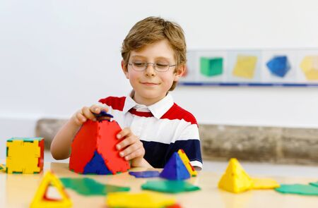 Happy kid boy with glasses having fun with building and creating geometric figures, learning mathematics and geometry