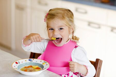 Adorable toddler girl eating healthy vegetable meal with potatoes and carrots soup for lunch. Cute happy baby child taking food at home or nursery daycare or kindergarten and learning using spoon.