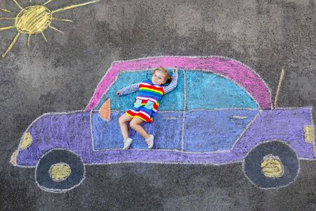 Adorable little toddler girl playing with colorful chalks and painting big car picture on asphalt. Happy baby child playing outside. Creative leisure for children outdoors in summer Reklamní fotografie